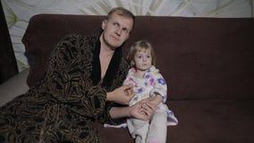 Небольшая дочь с ее отцом смотря интересный фильм с большими эмоциями акции видеоматериалы