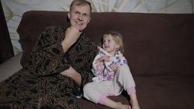 Небольшая дочь с ее отцом смотря интересный фильм с большими эмоциями сток-видео