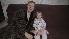 Небольшая дочь с ее отцом смотря интересный фильм с большими эмоциями видеоматериал