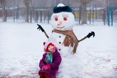 Небольшая жизнерадостная девушка около большого смешного снеговика Милая маленькая девочка имеет потеху в парке зимы стоковые изображения