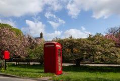 Небольшая коробка столба рядом с красной телефонной будкой стоковое фото