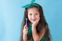 Небольшая красивая девушка очищает зубоврачевание зубной щетки зубов стоковая фотография rf
