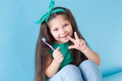 Небольшая красивая девушка очищает зубоврачевание зубной щетки зубов стоковое изображение