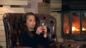 Небольшая милая девушка играя игры на смартфоне около камина сток-видео