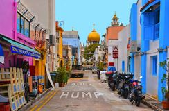 Небольшая улица со старыми красочными зданиями, мотоциклы и автомобили с хаотическим движением, старая мечеть с Golden Dome i стоковые фотографии rf