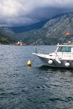 Небольшая шлюпка круиза для передачи к острову Gospa od Skrpjela причалила в Марине города Perast Островок на предпосылке Залив K стоковое фото rf