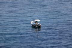 Небольшая шлюпка старта с людьми, голубым морем и небом стоковое фото rf