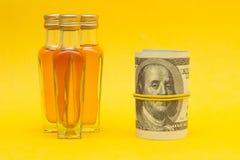 Небольшие бутылки с алкоголем на желтой предпосылке и долларах денег, выручках от продажи алкоголя, конца-вверх, фотографии стоковое фото