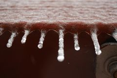 Небольшие замороженные сосульки качают от деревянной панели стоковые фото