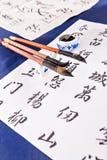 Небольшие кисти на таблице с белыми бумагами иллюстрация штока