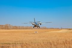 Небольшое воздушное судно для перехода земель пассажиров и парашютистов в поле на посадочной полосе с травой под голубым небом стоковое фото