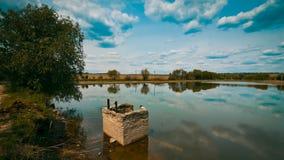 Небольшое озеро и поле, взгляд весны позднего утра с конструкцией стекания воды, облака и отражение в воде, фото природы Стоковое Фото