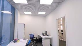 Небольшой взгляд офиса Не-работая время в офисе Современные компактная комната офиса с несколькими рабочих мест и яркий стоковая фотография rf