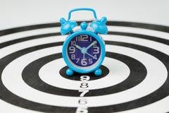 Небольшой голубой ретро будильник на разбивочном джэкпоте черно-белого dartboard круга использующ как время, цель или цель бизнес стоковое фото