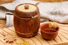 Небольшой деревянный бочонок с внутренностью меда и ложка на деревянном столе barrette жизнь деревенская все еще стоковые изображения