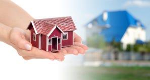 Небольшой дом в руках на предпосылке домов Стоковые Изображения