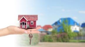 Небольшой дом в руках на предпосылке домов Стоковые Изображения RF