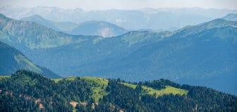 Небольшой дом поверх зеленого Ридж Несколько высоких горных цепей в помохе Krasnaya Polyana, Сочи, Кавказ, Россия стоковая фотография
