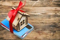 Небольшой дом с лентой на пуке пластичных карточек Стоковые Фото