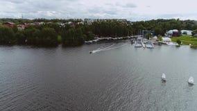 Небольшой залив на озере города См. пристань и шлюпки причаленные на ей сток-видео