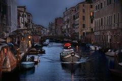 небольшой канал с меньшей шлюпкой с людьми с красным зонтиком и старыми домами в строке на сумраке в дождливом дне в Венеции, Ита стоковое изображение rf