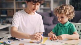 Небольшой мальчик помогая его дизайнеру матери создавая красочный бумажный коллаж дома сток-видео