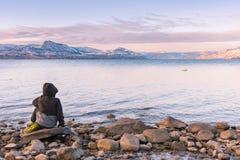 Небольшой мальчик сидит на утесе озером Okanagan с взглядом захода солнца гор покрытых снегом стоковые изображения