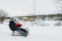 Небольшой мальчик sledding на зимнем времени нерезкость предпосылки запачкала движение frisbee задвижки скача к стоковые фотографии rf
