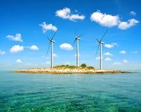 Небольшой остров с ветротурбинами в море стоковые изображения rf