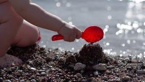 Небольшой ребенок выкапывает землю и строит замок на пляже в замедленном движении видеоматериал