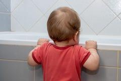 Небольшой ребенок в bathroom смотря в ванну, держа край стоковая фотография