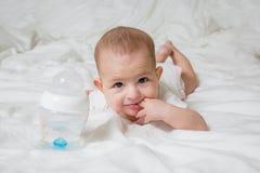 Небольшой ребенок лежит на белой кровати на его животе Девушка положила 2 пальца в ее рот Рядом пластиковая бутылка стоковое изображение rf