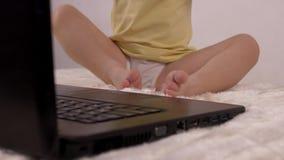 Небольшой ребенок отжимает палец на кнопке на клавиатуре ноутбука, конце-вверх, младенце и компьютере, релаксации сток-видео