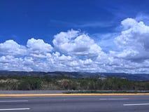 небо, горы, злаковики, и дорога Стоковые Изображения