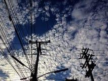 Небо заволакивает голубая линия электропередач Стоковые Изображения