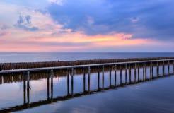 Небо захода солнца, строки бамбуковых ручек в море и мост цемента около святыни Matchanu, Phanthai Norasing, район Mueang Samut S Стоковая Фотография RF