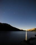 Небо звездной ночи над ровным озером с отражать автомобиля светлый поверхности Стоковое фото RF