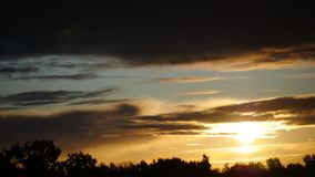 Небо промежутка времени восхода солнца и moving облака Латвия