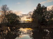 Небо света осени красивого солнца установленное над отражениями деревьев реки Стоковое Изображение