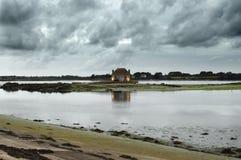 Небо с облаками и коттеджем отразило в море Стоковая Фотография RF