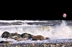 Небо черноты двигателя и свирепствуя океан с красочный отскакивать шарика пляжа мимо стоковые фото