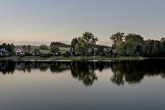 Небольшие дома на береге Lipno запруживают отражать в воде на заходе солнца вокруг древесин Стоковые Фото