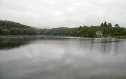 Небольшой дом около озера на дождливый день Стоковое Изображение RF