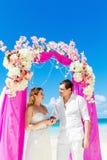 Невеста давая обручальное кольцо к его groom под deco свода Стоковая Фотография