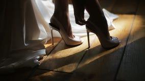 Невеста аранжирует ее ботинки свадьбы и покрывает их с белым платьем свадьбы Закройте вверх по взгляду акции видеоматериалы