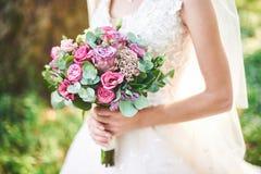 Невеста в белом платье держа букет фиолетовых цветков и растительности на предпосылке зеленой травы Стоковые Фото