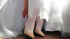 Невеста в белом платье кладет дальше ее ботинки для того чтобы выправить ее палец свадьбы концепции праздника образ жизни внутри  сток-видео