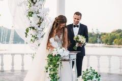 Невеста в белом платье на дне свадьбы кладет подпись около свода с озером на предпосылку Стойки новобрачных Стоковая Фотография