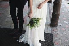 Невеста в белом платье держа букет фиолетовых цветков и растительности на предпосылке зеленой травы Стоковое Фото