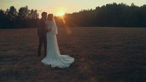 Невеста в платье свадьбы держа букет в поле с в лучами заходящего солнца акции видеоматериалы